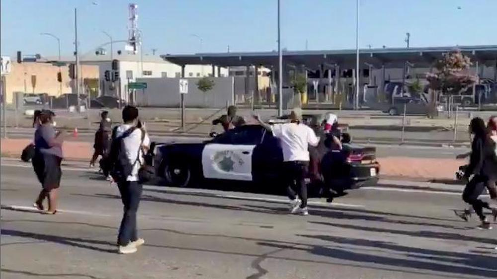 Protester falls off police car during protest over Floyd's death